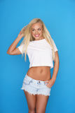 Trendy young blond woman in denim shorts Royalty Free Stock Photos