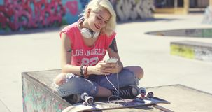 Trendy young blond woman at a skate park. Sitting on a graffiti covered wall with her skateboard choosing a tune to listen to on her mobile phone stock video