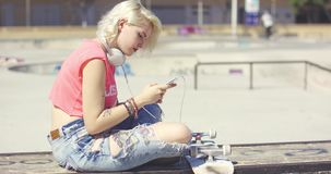 Trendy young blond woman at a skate park. Sitting on a graffiti covered wall with her skateboard choosing a tune to listen to on her mobile phone stock footage