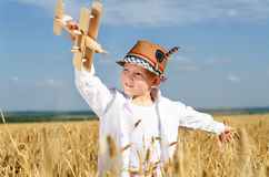 Trendy young boy playing in a field with a plane Stock Photos
