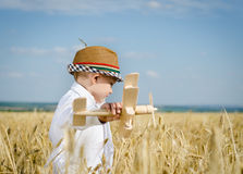 Trendy young boy playing in a field with a plane Stock Photo