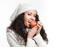 Trendy young brunette woman biting an apple. And smiling Royalty Free Stock Image