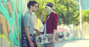 Trendy young couple chatting in an urban street. Trendy young couple with skateboards standing chatting in an urban street with a curving wall covered in stock video footage