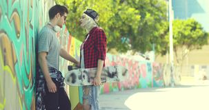 Trendy young couple chatting in an urban street. Trendy young couple with skateboards standing chatting in an urban street with a curving wall covered in stock video