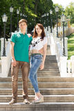 Trendy young couple posing on a flight of stairs. Trendy young couple posing on a steep flight of stairs in an outdoor park leading back up a steep hillside Royalty Free Stock Photos