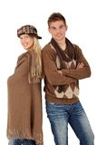 Trendy young couple posing in winter clothes. Wearing scarf, hat, smiling at camera Stock Image