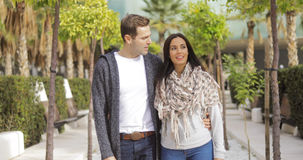 Trendy young couple walking along a promenade Royalty Free Stock Images
