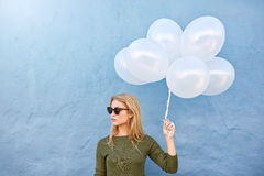 Trendy young female with balloons Stock Images