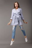 Trendy Young Female Jumping in Blue Coat stock images