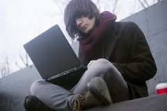 Freelancer using laptop. The trendy young freelancer guy with long hair is using laptop outdoors stock photos