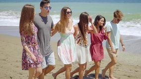 Trendy young friends strolling barefoot on a beach. With their arms linked smiling and laughing stock video footage
