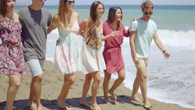 Trendy young friends strolling barefoot on a beach. With their arms linked smiling and laughing stock video