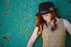 Trendy young girl in hat. Trendy young redheaded girl in fashionable hat; rusted metal surface in background with copy space Stock Image