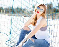 Trendy young girl posing against a background of blue football g Royalty Free Stock Photos