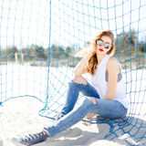 Trendy young girl posing against a background of blue football g Stock Images