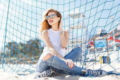 Trendy young girl posing against a background of blue football g Stock Image