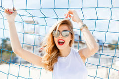Trendy young girl posing against a background of blue football g Royalty Free Stock Images