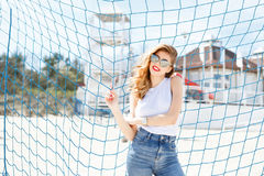 Trendy young girl posing against a background of blue football g Royalty Free Stock Photo