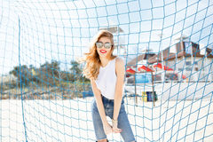 Trendy young girl posing against a background of blue football g Royalty Free Stock Image