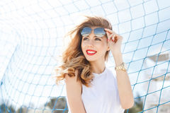 Trendy young girl posing against a background of blue football g Stock Photo