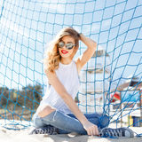 Trendy young girl posing against a background of blue football g Stock Photos