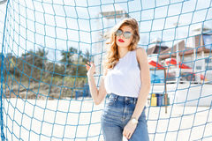 Trendy young girl posing against a background of blue football g Royalty Free Stock Photography
