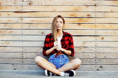 Trendy young girl posing against wooden wall background. Modern Royalty Free Stock Photography