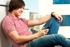 Trendy young guy typing a message. Portrait of a trendy young guy typing a message on mobile phone Stock Image