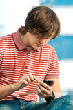 Trendy young guy typing a message on mobile Stock Image