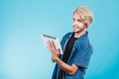 Trendy young guy using tablet computer Stock Photos