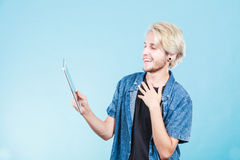 Trendy young guy using tablet computer Royalty Free Stock Image