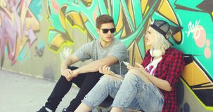 Trendy young hipster couple sitting in the street. Relaxing on the sidewalk chatting in front of colorful graffiti  with copy space stock footage