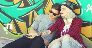 Trendy young hipster couple taking a selfie. Using a mobile on a stick as they pose together in the summer sun in front of colorful graffiti stock video footage