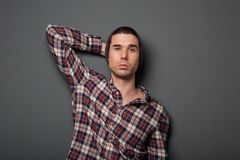 Trendy young man in checkered shirt and hat Stock Image