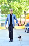 Trendy young man with a dog Stock Images