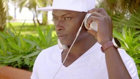 Trendy young man enjoying his music. Trendy young man in a white outfit and baseball cap enjoying his music on a set of headphones with his eyes closed in bliss stock video footage