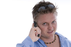 Trendy young man with mobile. Telephone and sunglasses on forehead, isolated on white background with copy space Royalty Free Stock Images