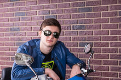 Trendy young man on a motorbike Stock Images