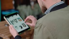 Man shopping online on sales. Trendy young man sitting outside on a cafe terrace and surfing web on his fancy tablet. Man on e-commerce website choosing clothes stock video footage