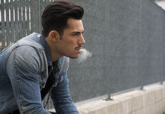 Trendy young man sitting outside smoking Stock Images