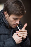 Trendy young man smoking cigarette. Stock Image