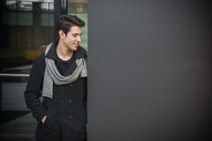 Trendy young man standing against wall in urban environment Royalty Free Stock Photo