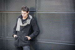 Trendy young man in winter fashion against wall in urban environment Stock Images