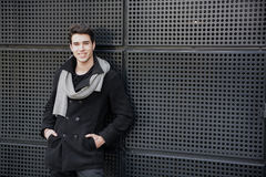 Trendy young man in winter fashion against wall in urban environment Stock Image