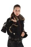 Trendy young model. A trendy young model with a ponytail hairstyle wears a black jacket with fur collar Royalty Free Stock Images