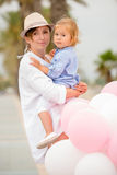 Trendy young mother holding her young daughter Stock Images