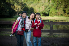 Trendy young mum and two teenagers standing near ranch Stock Images