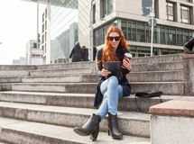 Trendy young red headed woman with cup in hand. Trendy young red head wearing black boots and blue jeans seated on concrete steps smiles at her tablet on a sunny Royalty Free Stock Image