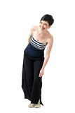 Trendy young short hair woman in wide-leg pants leaning and laughing. Full body length portrait isolated over white studio background Royalty Free Stock Photography