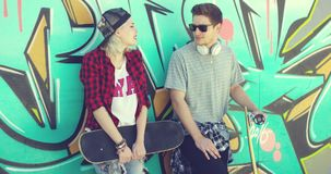 Trendy young skateboarders standing chatting. Leaning against a colorful graffiti wall with a young woman in a baseball cap and handsome young man in sunglasses stock video footage